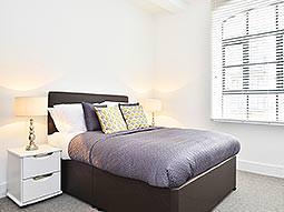 A luxurious boudoir looking bedroom with metallic bedding