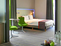 A double bed, with green chairs and a table in the foreground