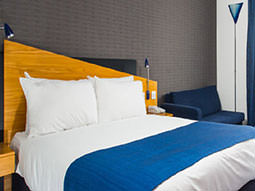 A double bed with a blue throw placed on top, in a hotel room