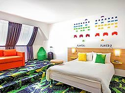 A white double bed with an orange sofa in the background, in a room with a vibrant green carpet and Space Invader stencils on the wall