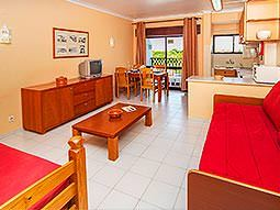 Two red sofas around a coffee table in the foreground, with a set of drawers, a dining table and kitchenette in the back