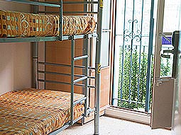 Bunkbeds next to open French doors, leading out onto a balcony