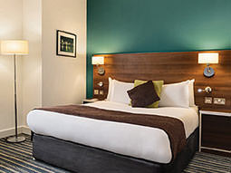 A double bed in a green hotel room