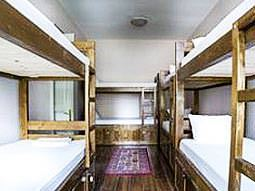 Some bunk beds lining the walls in a room with wooden floorboards