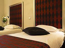 A twin room with brown and black bedding and decorations on the wall