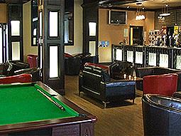 Leather chairs and sofas in front of a bar, with a snooker table in the foreground