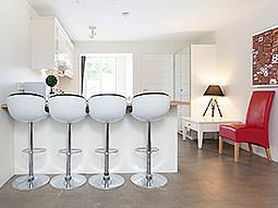 Four white bar stool seats in a modern kitchen