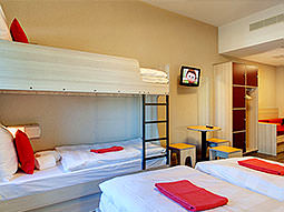 A bunk bed and two single beds in a room with white bedding and red towels on the bed