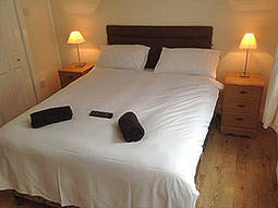 A white double bed with towels and a remote on top