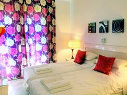 Two single beds with red cushions on, and bright purple and pink curtains drawn