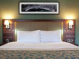 A double bed with a photograph hung above it