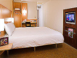 A white double bed in a hotel room, with a desk and cupboard in the background, facing a TV in the wall