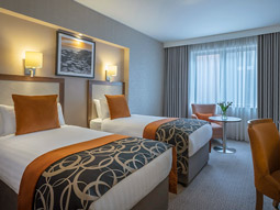 A double bed in a grand hotel room featuring purple and gold wallpaper, facing a desk and purple desk chair