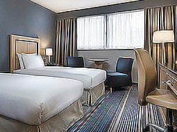 Two white single beds in a blue hotel room, with a desk, desk chairs, two blue chairs and a table in the background