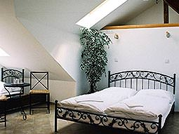 A double bed in a white room with high ceilings