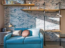 A blue sofa with shelves behind and bright wallpaper
