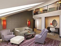 Chairs and a sofa around a coffee table in a suite, with an upper level in the background