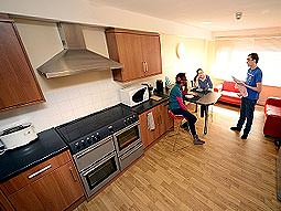 People stood in the kitchen of an apartment, with seating in the background
