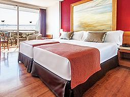 Two beds pushed together in a bedroom with french windows behind and a painting mounted on the wall behind the beds