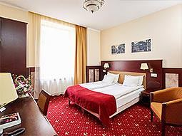 A spacious double room with red and gold colour scheme