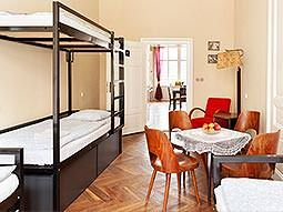 Black bunkbeds on the side of a room, with tables and chairs on the side of the room