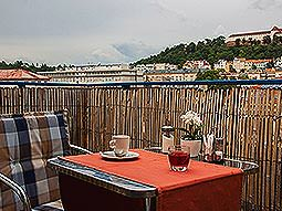 A seat and a table with coffee on it, on a picturesque balcony
