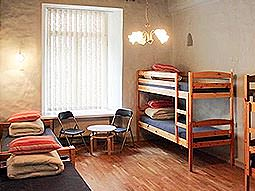 A large room with twin beds, bunk beds and a table and chairs