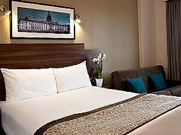 A double bed with a panramic photograph hung above it