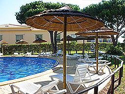 Sun loungers under a parasol, around an outdoor pool