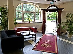Two sofas facing a coffee table and a red carpet leading to an open door