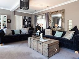 Two black sofas, with cushions on top, and a coffee table in the middle in a large living room