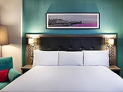 A picture hanging above a white bed in a blue hotel room