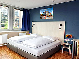 Two single white beds in a blue hotel room, with a bedside table and desk to one side of the bed