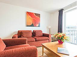 Two red sofas around a coffee table, in an apartment