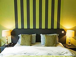 A double bed against a green and black striped wall
