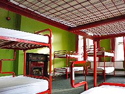 A green-walled room with red metal framed bunk beds
