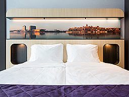 A white double bed, topped with a purple throw, with a pitcure above the bed