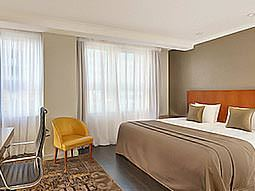 A room with two large windows, a double bed and two seats