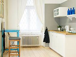 A white kitchenette opposite a blue table and stool