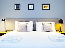 Three small pictures above a large, white bed with towels folded up on top
