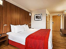 A spacious double room in Ramada Encore Gateshead Quays, with wood paneling and wooden floorboards