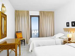 A twin room with white bedding and a view from the balcony
