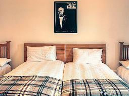 Two single beds pushed together with a Godfather poster over the bedhead