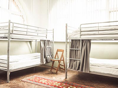 Two bunk beds in a dorm room at Hatters Manchester City Centre, with a wooden chair in between