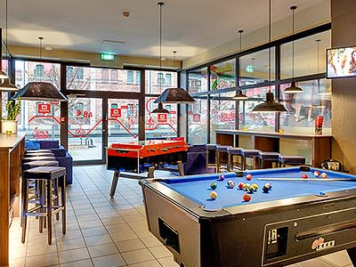 A pool table in the foreground, with table football and bar stools in the background