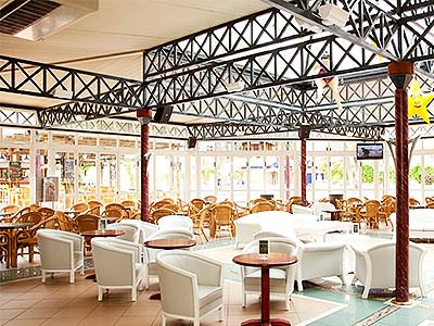 White chairs and tables under a large canopy