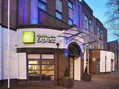 Exterior and entrance of the Holiday Inn Express Queens Quarter, at night