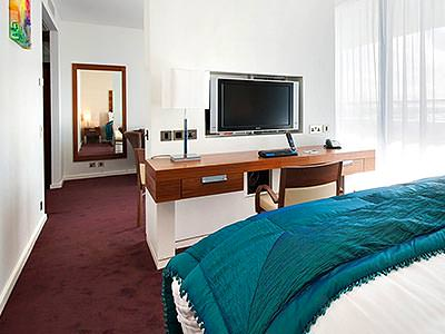 A double bed with a blue throw, facing a desk and TV with a mirror on the wall in the back