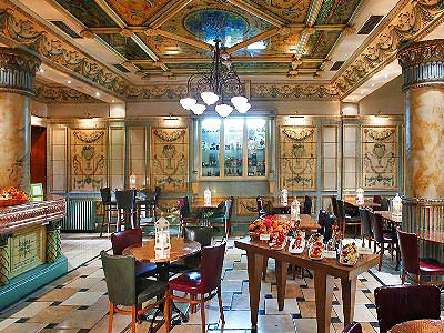 Several tables and chairs set up for dinner in the grand hotel restaurant at Imperial Hotel Cork, with columns and a marble ceiling