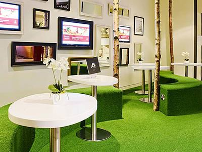 Close up of tables and green seats on a green carpet, in front of a wall lined with pictures